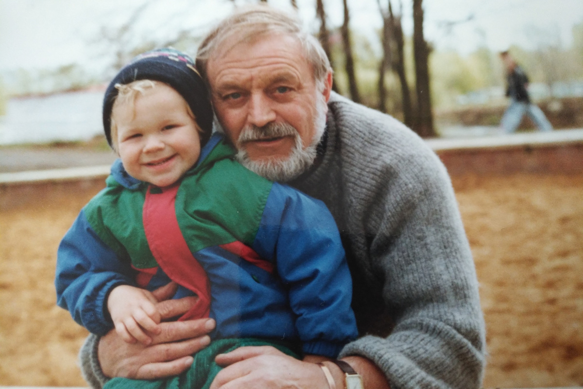 A picture of me and my grandad when I was about 18 months old, we're outside and I'm laughing.