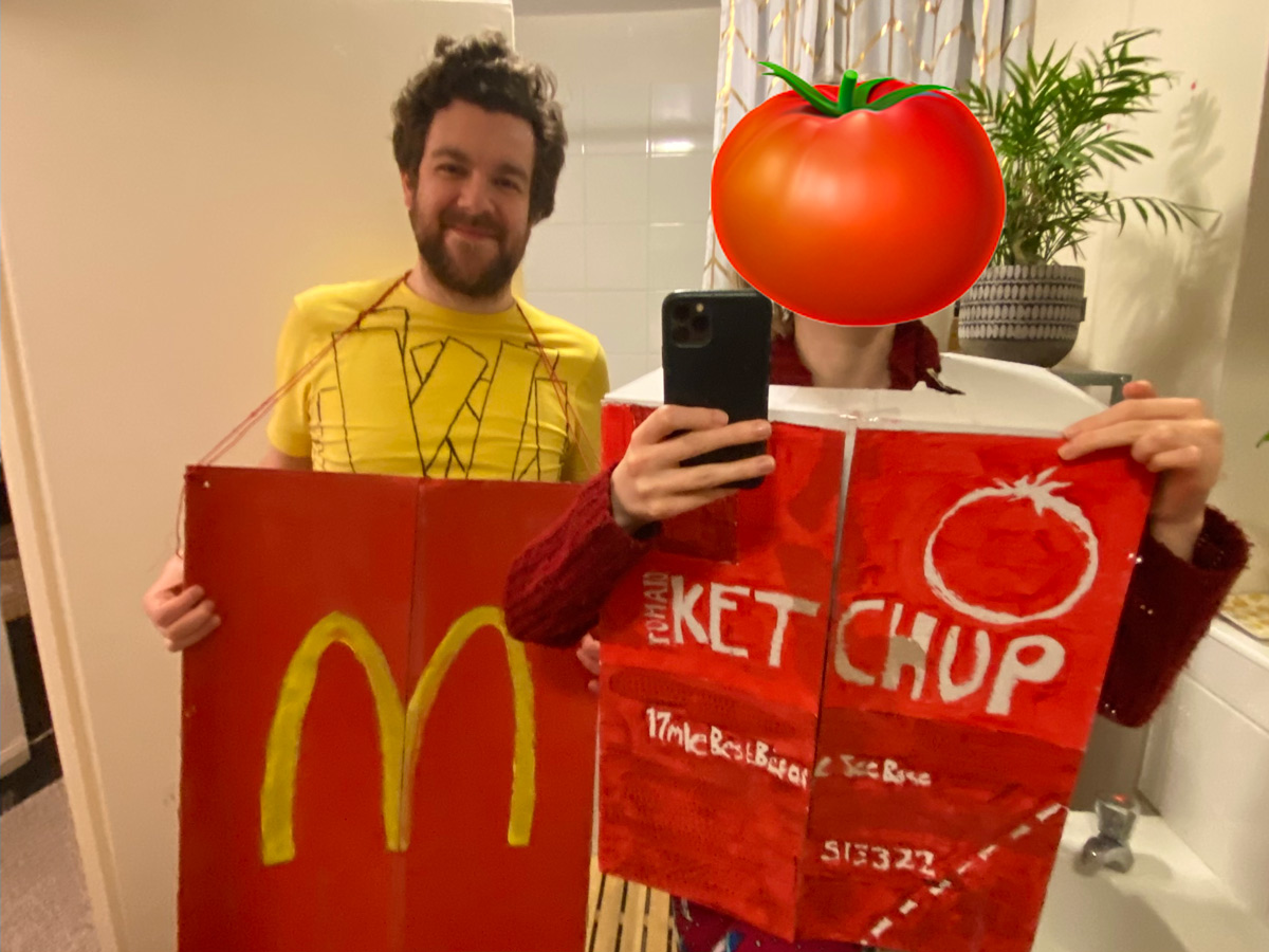 Rowan and Charlotte dressed as takeaway items. Rowan is dressed as McDonalds fries, wearing a yellow T-Shirt with chips drawn onto it and a large red box. Charlotte is dressed as a tub of ketchup in a painted box.
