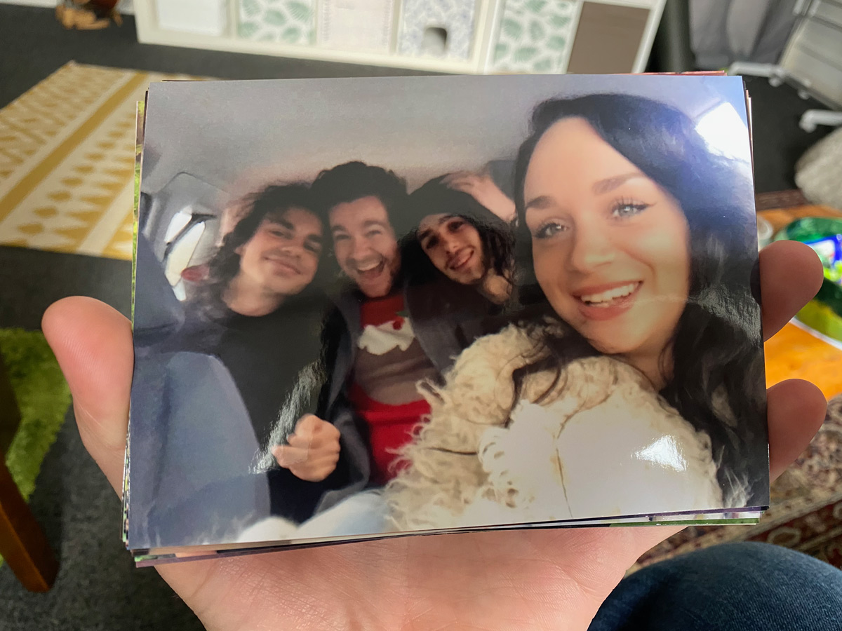 A selfie taken from the front seat of a car. Rowan's sister is holding the camera, and on the back seat there's Rowan with his arms around his two brothers. They're all smiling, and Rowan's wearing a Christmas jumper.