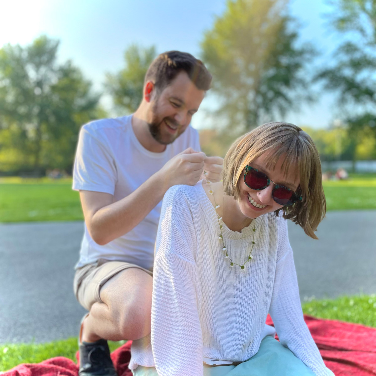 Rowan kneeling down and putting a daisy chain around Charlotte's neck, they're sat on a picnic blanket in a sunny park