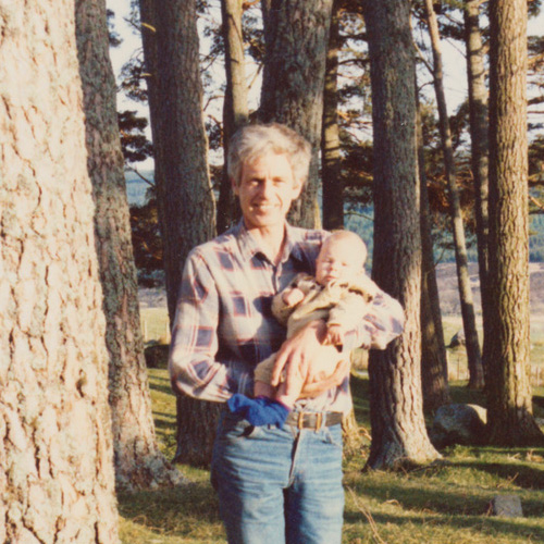 My dad standing amongst trees and holding me as a baby