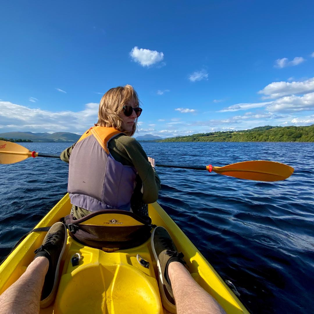 The view from the back seat of a twin kayak with Charlotte paddling and the shore of Loch Lomond in the background