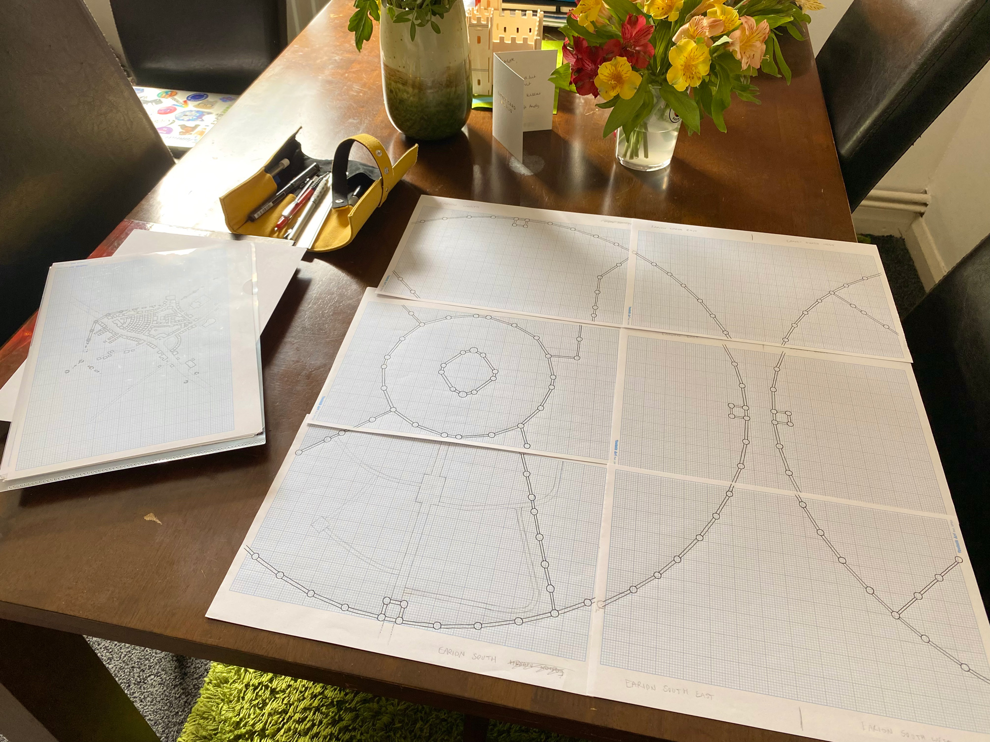 Six sheets of A4 grid paper laid out with city walls drawn in a large circle across all of them.