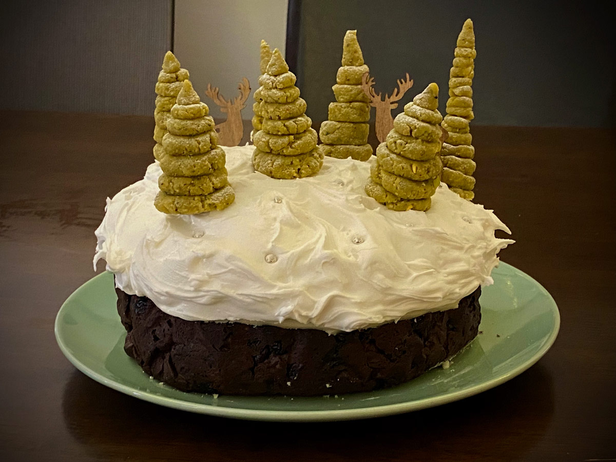 A Christmas cake, decorated with heaps of royal icing that looks like snow. Small green trees made from pistachio paste are scattered across the top, with two wooden stags peeking around them